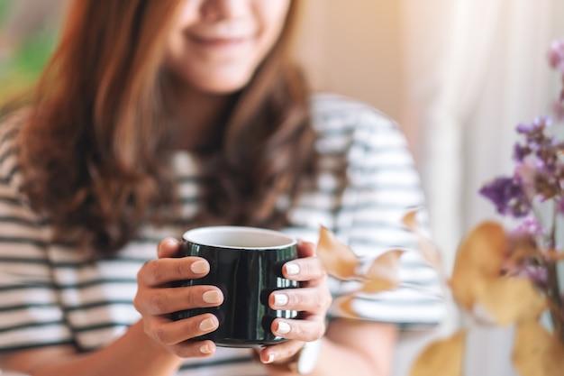 마시는 뜨거운 커피의 검은 컵을 들고 아름 다운 여자의 근접 촬영 이미지