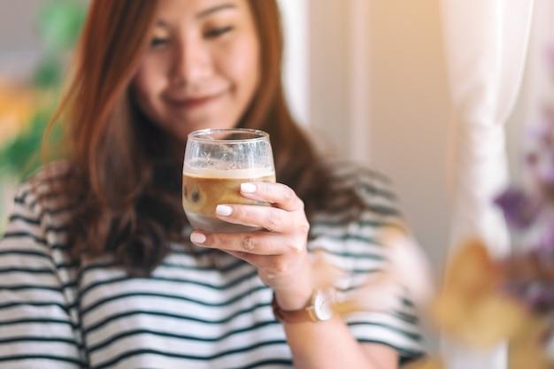 Крупным планом изображение красивой женщины, держащей стакан холодного кофе, чтобы выпить в кафе