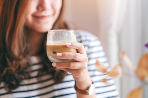 카페에서 마실 아이스 커피 한 잔을 들고 있는 아름다운 여성의 클로즈업 이미지