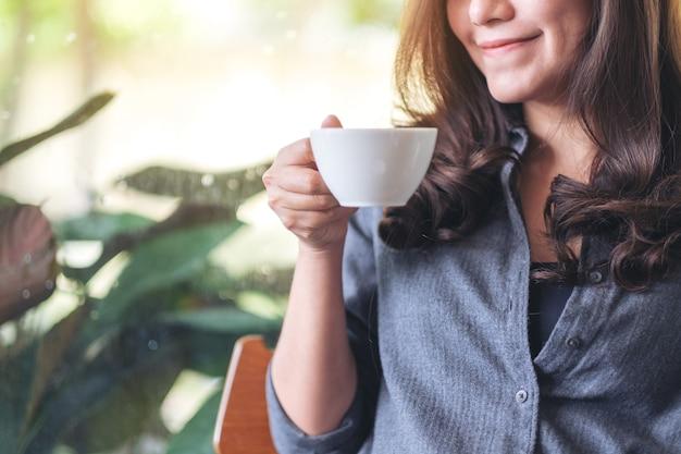 카페에서 뜨거운 커피를 들고 마시는 아름다운 여성의 클로즈업 이미지