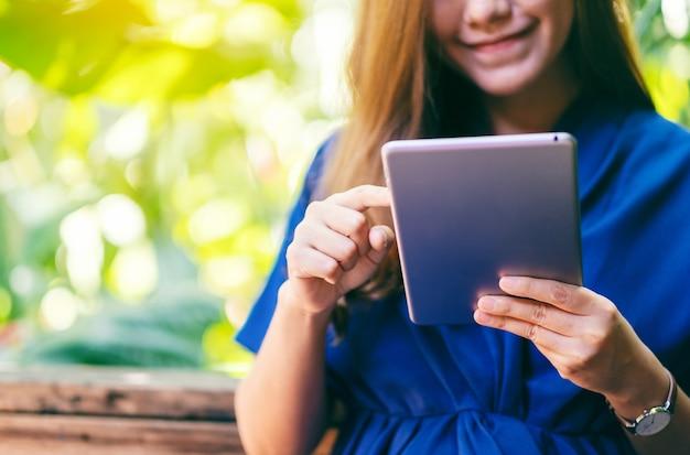 Крупным планом изображение красивой женщины, держащей и использующей планшетный пк, сидя в саду