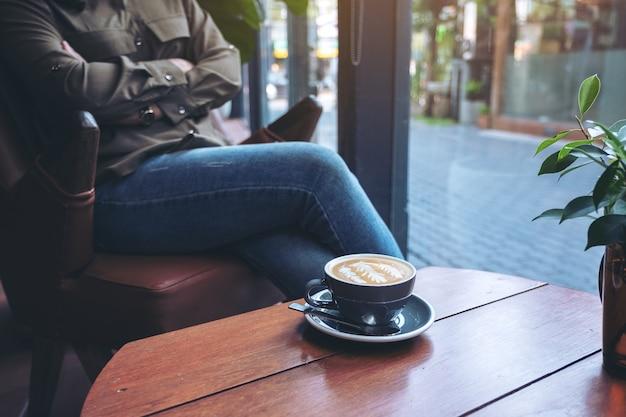 여자가 카페에 앉아 나무 테이블에 뜨거운 라떼 커피의 파란색 컵의 근접 촬영 이미지