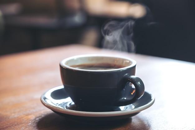 Изображение крупного плана голубые чашки горячего кофе с дымом на винтажном деревянном столе в кафе