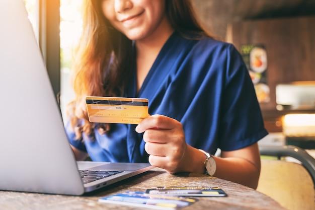 노트북 컴퓨터를 사용하는 동안 신용 카드를 들고 있는 비즈니스 여성의 클로즈업 이미지