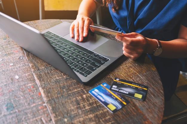 ラップトップコンピューターを使用しながらクレジットカードを保持しているビジネス女性のクローズアップ画像