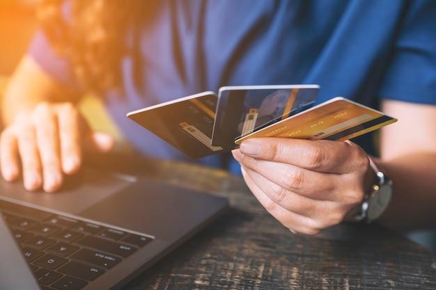 노트북 컴퓨터를 사용하는 동안 신용 카드를 들고 있는 비즈니스 여성의 근접 촬영 이미지
