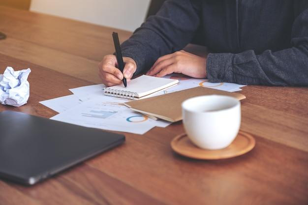 Крупным планом изображение бизнес-леди, работающей и записывающей на белом пустом блокноте с испорченными бумагами и ноутбуком на столе в офисе
