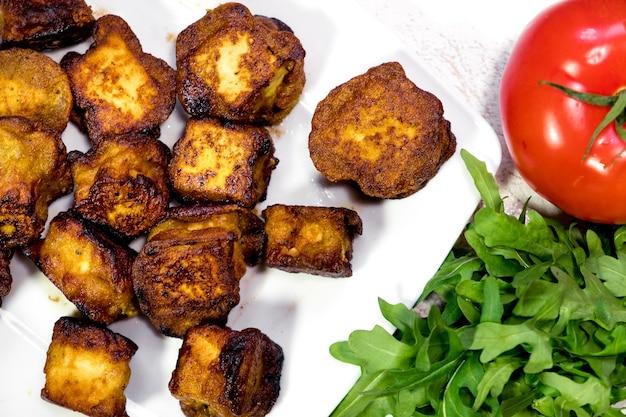 토마토와 함께 접시에 맛있는 기 튀긴 인도 코티지 치즈 조각의 근접 촬영 이미지