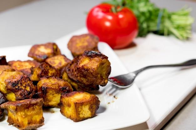접시에 맛있는 기 튀긴 인도 코티지 치즈 조각의 근접 촬영 이미지