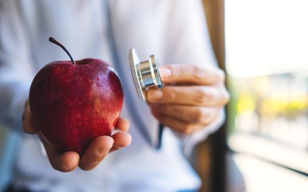 Крупным планом изображение врача, использующего стетоскоп, чтобы исследовать красное яблоко