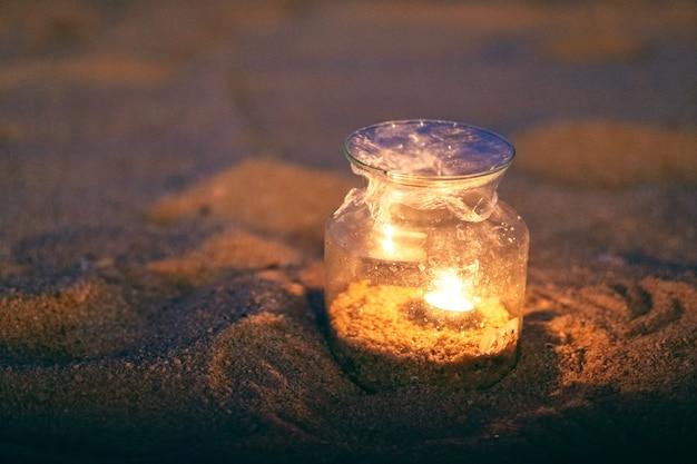 夜のビーチでガラス瓶キャンドルホルダーのクローズアップ画像