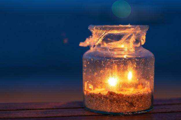 夜のビーチのそばの木製テーブルの上のガラス瓶キャンドルホルダーのクローズアップ画像