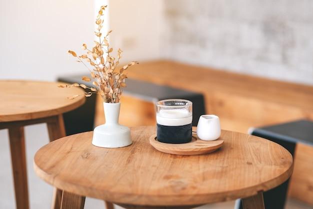 최소한의 카페에서 나무 테이블에 라떼 커피 한 잔의 근접 촬영 이미지