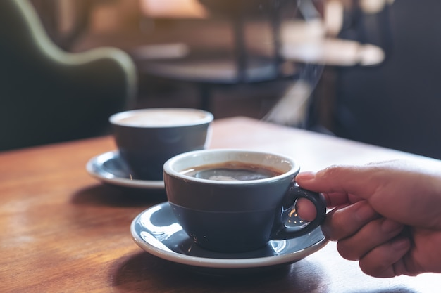 Изображение крупного плана руки держа голубую чашку горячего кофе с дымом на деревянном столе в кафе