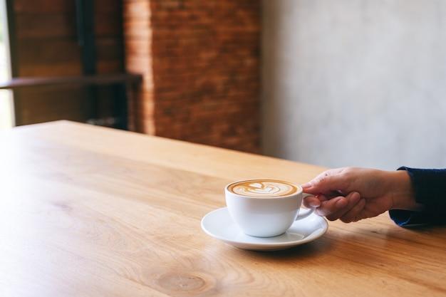 나무 탁자에 뜨거운 커피 한 잔을 들고 있는 손의 클로즈업 이미지