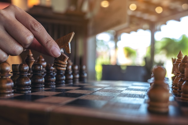 Крупным планом изображение руки, держащей и перемещающей лошадь в деревянной шахматной игре