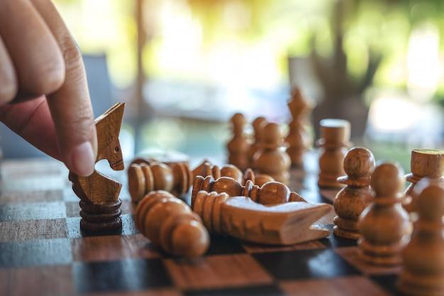 Крупным планом изображение руки, держащей и перемещающей лошадь, чтобы выиграть другую лошадь в деревянной шахматной игре