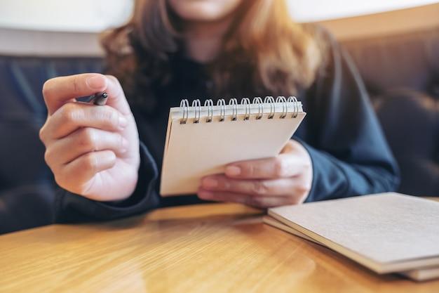 Крупным планом изображение руки, держащей и пишущей на пустой записной книжке на столе в кафе