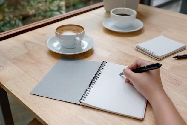 Изображение крупного плана руки записывая вниз на белой пустой тетради с кофейной чашкой на деревянном столе