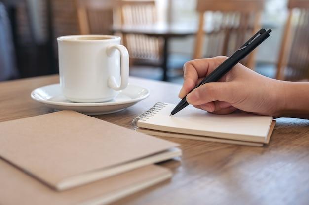 Крупным планом изображение рукописного ввода на пустой блокнот с чашкой кофе на столе в кафе