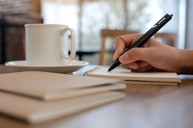 カフェのテーブルにコーヒーカップと空白のノートに手書きのクローズアップ画像