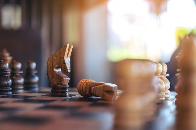 馬のクローズアップ画像は木製のチェス盤で別のチェスを獲得します。