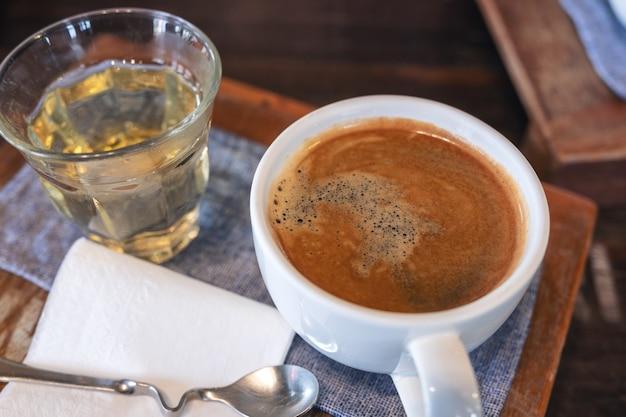 Крупным планом изображение белой чашки горячего кофе и стакана чая на старинный деревянный стол в кафе