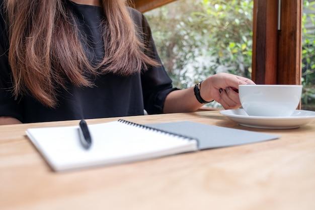 Изображение крупного плана женщины держа чашку кофе с тетрадью и ручку на деревянном столе