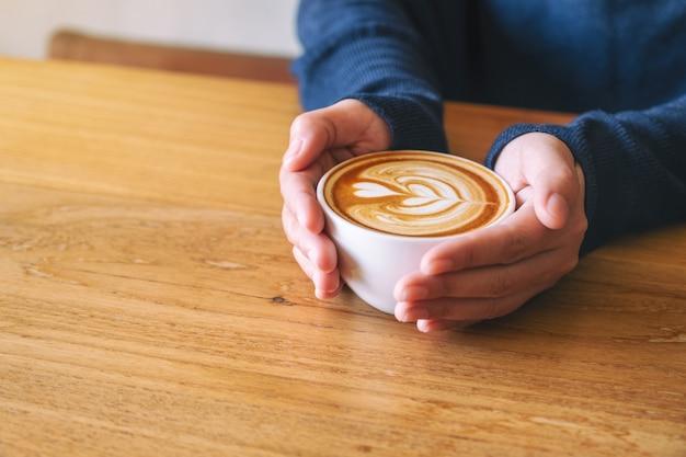 나무 탁자에 뜨거운 커피 한 잔을 들고 있는 여성의 클로즈업 이미지