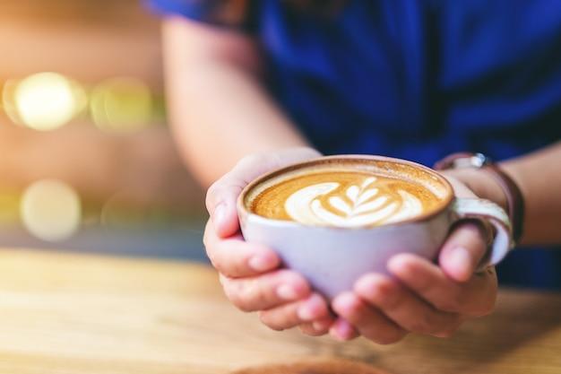 나무 탁자에 뜨거운 라떼 커피 한 잔을 들고 있는 여성의 클로즈업 이미지