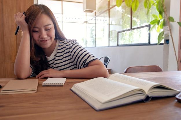 勉強しながらノートや木製のテーブルの教科書に書くためにペンを持っている女性のクローズアップ画像