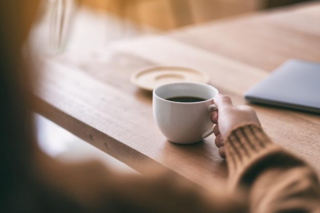 마시는 뜨거운 커피의 흰색 컵을 들고 여자의 근접 촬영 이미지