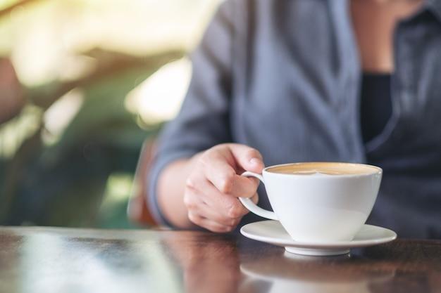카페에서 뜨거운 커피를 들고 마시는 여성의 근접 촬영 이미지