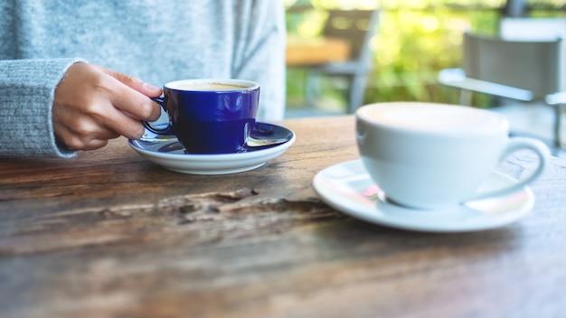 屋外でホットコーヒーを保持し、飲んでいる女性のクローズアップ画像