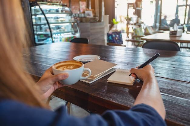 Крупным планом изображение женщины, держащей и пьющей горячий кофе во время записи на блокноте на деревянном столе в кафе