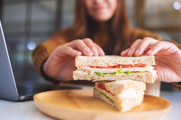 ラップトップコンピューターで作業しながら全粒小麦のサンドイッチを持って食べている女性のクローズアップ画像