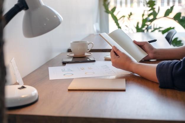 테이블에 커피 컵과 서류와 함께 빈 노트북을 들고 여는 여자의 근접 촬영 이미지