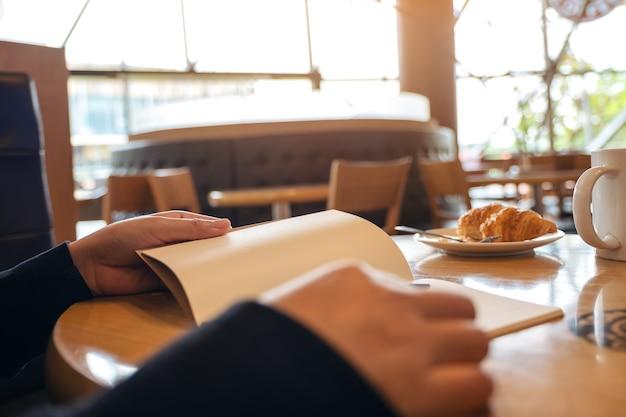 Крупным планом изображение женщины, держащей и читающей книгу с круассаном в тарелке на деревянном столе