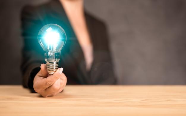 白熱電球の革新と創造性を保持し、示している女性のクローズアップ画像