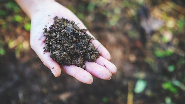 耕作可能な土壌を手に持って見せている女性のクローズアップ画像