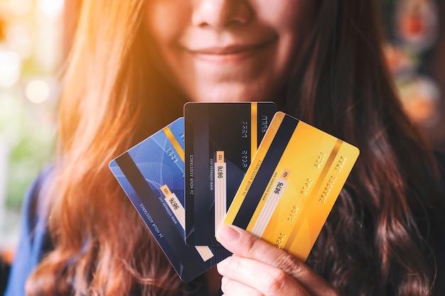 クレジットカードを保持し、表示している女性のクローズアップ画像