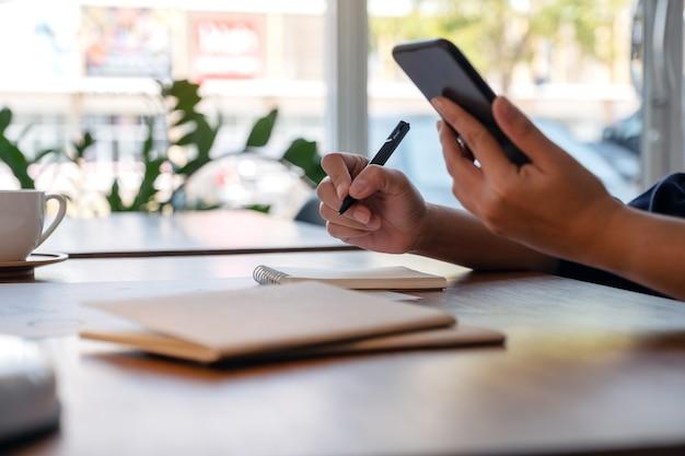 Крупным планом изображение женщины, держащей и использующей мобильный телефон во время работы в офисе