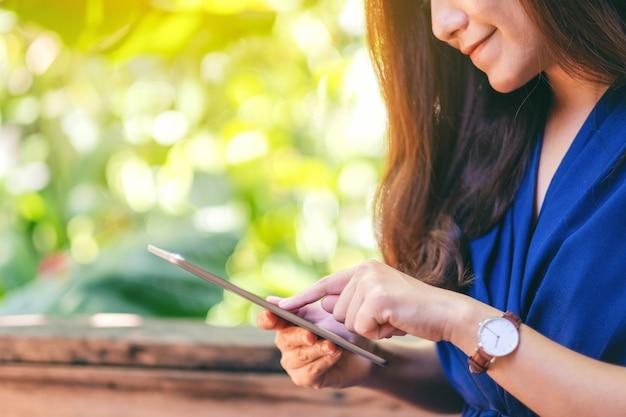 Крупным планом изображение женщины, держащей и использующей планшетный пк, сидя в саду