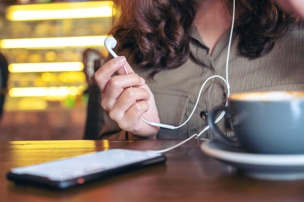 Крупным планом изображение женщины, держащей наушники, слушая музыку с мобильного телефона в кафе