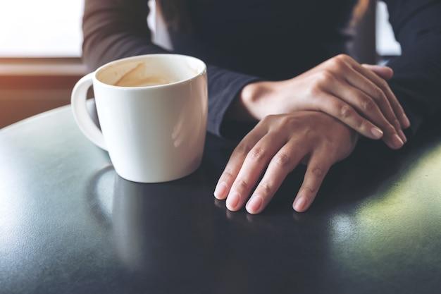 手を持ち、カフェでホットコーヒーを飲む女性の拡大画像