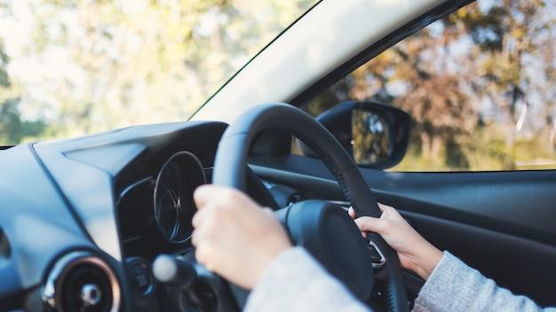Крупным планом изображение женщины, держащей рулевое колесо за рулем автомобиля на дороге