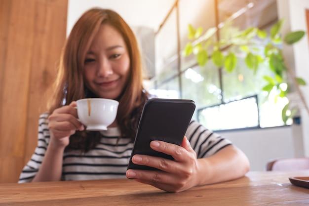Крупным планом изображение женщины, держащей, использующей и смотрящей на смартфон во время питья кофе