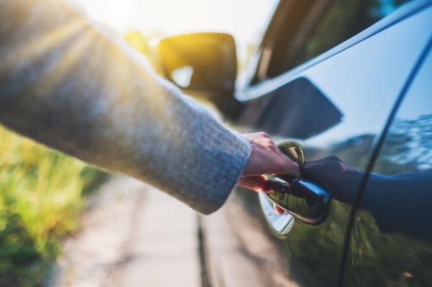 Крупным планом изображение женщины, открывающей двери автомобиля