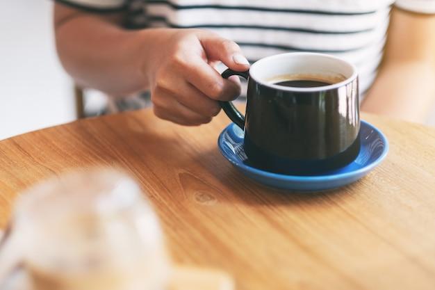 Крупным планом изображение женской руки, держащей черную чашку горячего кофе на деревянном столе