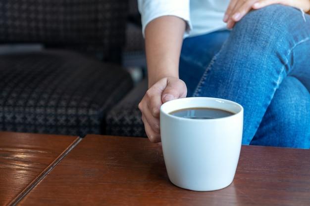 カフェに座って飲むためにホットコーヒーのカップを持っている女性の手のクローズアップ画像